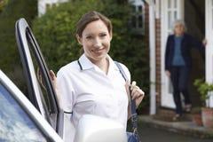 Женский работник заботы навещая старшая женщина дома