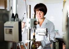 Женский работник используя машину для того чтобы cork вино Стоковое Изображение RF