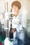 Женский работник используя машину для того чтобы cork вино Стоковое фото RF