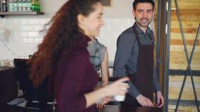 Женский работник кофейни принимает nfc оплат мобильного телефона от радостных клиентов и продает стекла выноса акции видеоматериалы