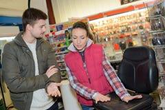 Женский работник магазина оборудования помогает клиенту делая выбор стоковые фото