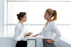Женский работник объясняя к ее неудовлетворенному боссу почему она была последней для работы пока стоящ в интерьере офиса, Стоковое Изображение RF