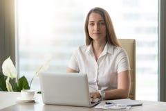 Женский работник офиса делая ежедневную работу на компьтер-книжке Стоковая Фотография