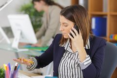 Женский работник офиса имея переговор на телефоне стоковые фотографии rf