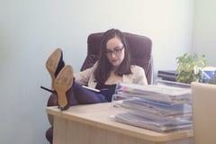 Женский работник офиса сидит в кожаном стуле, ногах на таблице рассматривая рабочий план Стоковые Фото