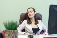 Женский работник офиса сидит в кожаном стуле перед компьютером и думает Стоковое Фото