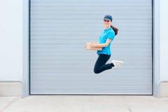 Женский работник поставки скача перед складом хранения Стоковые Фото