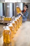 Женский работник проверяя бутылки масла Стоковые Фотографии RF