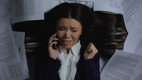 Женский работник слушая для того чтобы хозяйничать заказы по телефону, ужаснутому количества работы видеоматериал
