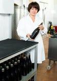 Женский работник сортируя бутылки вина Стоковые Изображения RF