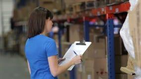 Женский работник с доской сзажимом для бумаги в складе акции видеоматериалы