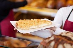 Женский работник хлебопекарни держа поднос сладостного хлеба Стоковое фото RF