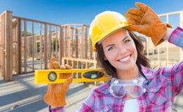 Женский рабочий-строитель держа вровень нося перчатки, трудный Ha Стоковое Изображение