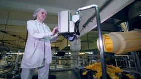 Женский регулятор работает с оборудованием фабрики, которое двигает картофельные чипсы, замедленное движение видеоматериал