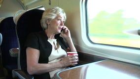 Женский регулярный пассажир пригородных поездов с кофе на поезде используя мобильный телефон акции видеоматериалы