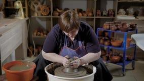 Женский ремесленник делает процесс бросать пробела глины на вращая turntable в магазине гончарни с керамическим сток-видео