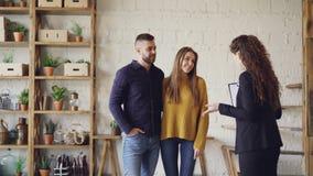 Женский риэлтор в костюме показывает квартиру стиля просторной квартиры к молодому человеку и женщине ища новая квартира Покупате сток-видео