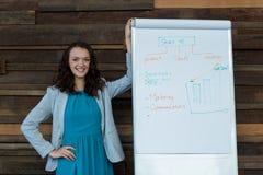 Женский руководитель бизнеса стоя близко диаграмма сальто Стоковое Изображение RF