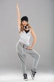 Женский самомоднейший танцор представляя на сером цвете Стоковые Изображения