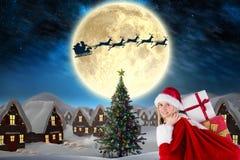 Женский Санта Клаус стоя против цифров произведенной предпосылки Стоковые Фото
