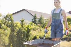 Женский садовник нажимая тачку на питомнике завода Стоковое фото RF