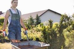 Женский садовник нажимая тачку на питомнике завода Стоковая Фотография