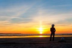 Женский силуэт велосипедиста стоя на пестротканом заходе солнца Голубой sk Стоковые Изображения