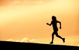 Женский силуэт бегуна, бежать в заход солнца Стоковые Фото