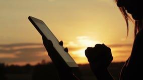 Женский силуэт используя цифровую таблетку в лесе на заходе солнца видеоматериал