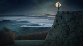Женский силуэт против луны в горе стоковая фотография