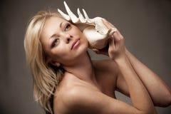 женский слушая seashell моря к Стоковые Изображения