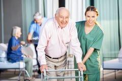 Женский смотритель помогая старшему человеку в использовании Стоковые Фотографии RF