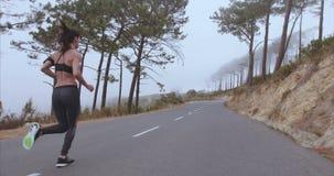 Женский спортсмен бегуна sprinting на проселочной дороге сток-видео