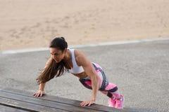 Женский спортсмен фитнеса делать нажимает поднимает разминку снаружи стоковая фотография
