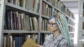 Женский студент колледжа хипстера ищет книга на книжной полка акции видеоматериалы