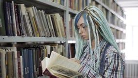 Женский студент колледжа хипстера с dreadlocks ищет книга на книжной полка сток-видео