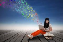 Женский студент изучая с компьтер-книжкой Стоковые Фото