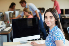 Женский студент колледжа используя компьютер в классе Стоковая Фотография