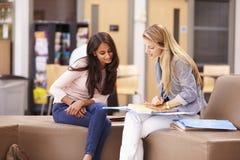 Женский студент колледжа работая с ментором Стоковые Фото