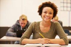 Женский студент средней школы изучая на столе в классе Стоковая Фотография RF