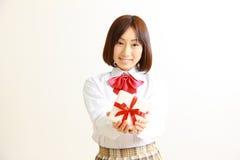 Женский студент средней школы предлагая подарок Стоковые Изображения RF