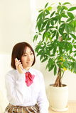 Женский студент средней школы разговаривает с умным телефоном Стоковые Изображения RF