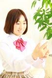 Женский студент средней школы разговаривает с умным телефоном Стоковые Фото