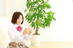 Женский студент средней школы разговаривает с умным телефоном Стоковые Изображения