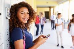 Женский студент средней школы шкафчиками используя мобильный телефон