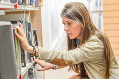 Женский студент университета в библиотеке Стоковые Фотографии RF