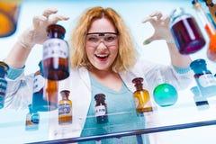 Женский студент химии с склянкой испытания стеклоизделия Стоковые Фото