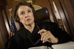 Женский судья сидя в зале судебных заседаний стоковые фотографии rf
