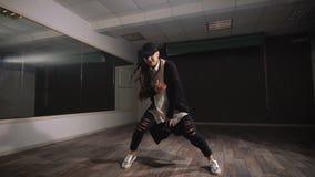 Женский танцор в белой рубашке, черных брюках и черной крышке показывая джазу современные танцы Девушка выразительно танцует и сток-видео