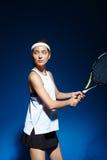 Женский теннисист с ракеткой готовой для того чтобы ударить шарик Стоковое Изображение RF